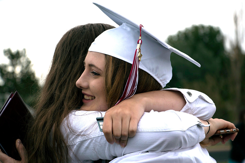. Ellie Walton, left, hugs her friend in celebration of graduating class of 2017 from Berthoud High School on Saturday, May 28th. (Michelle Risinger/ Loveland Reporter-Herald)