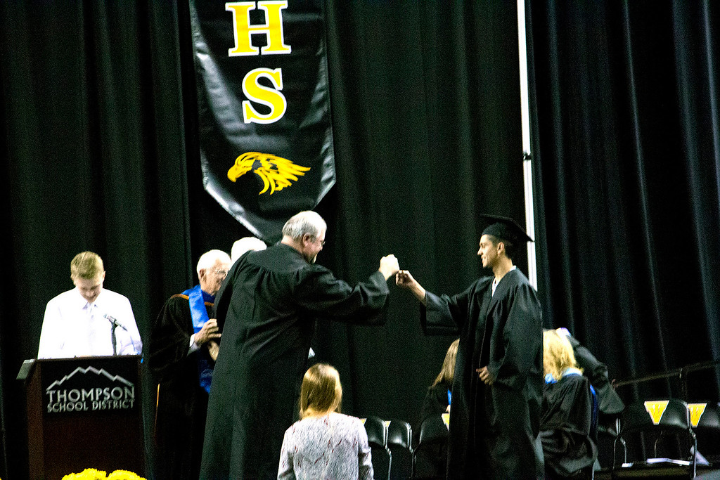 . Julian Espinoza, right, fist bumps with Dr. Stan Scheer, district superintendent at the Thompson Valley High School graduation Ceremony at the Budweiser Events Center on Saturday, May 28, 2017. (Michelle Risinger/ Loveland Reporter-Herald)