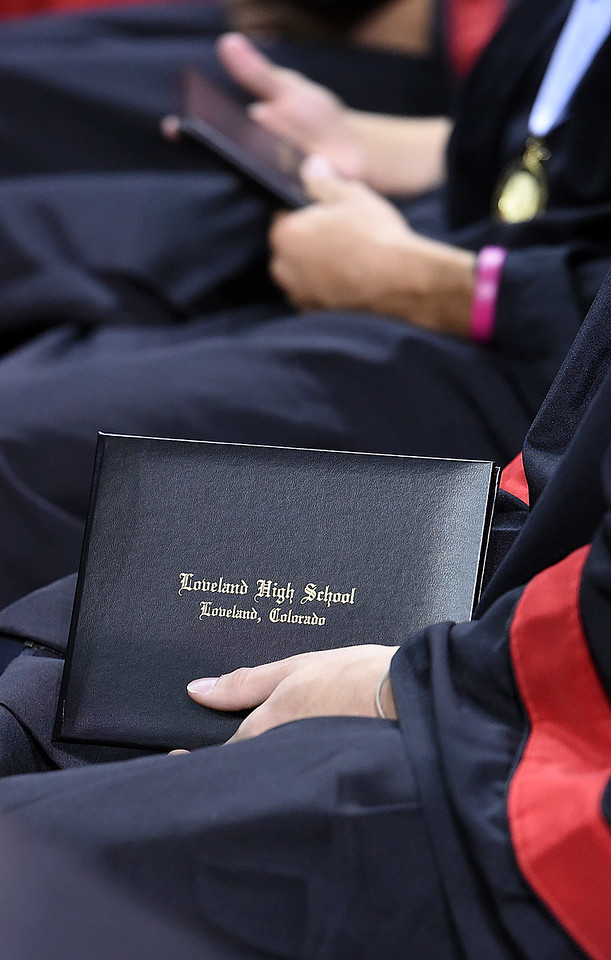 A Loveland High School graduate holds his diploma during his commencement ceremony Saturday, May 27, 2017, at the Budweiser Event Center in Loveland. (Photo by Jenny Sparks/Loveland Reporter-Herald)