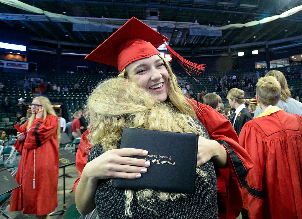 . Loveland High School graduate Morgan Sehi gets a hug from her friend, Kyndall Ostreim moments after her commencement ceremony Saturday, May 27, 2017, at the Budweiser Event Center in Loveland. (Photo by Jenny Sparks/Loveland Reporter-Herald)