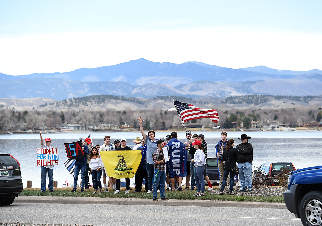 . Thompson School District students hold signs supporting gun rights Friday, March 23, 2018, across the street from where other students rally at Dwayne Webster Veterans Park in Loveland to show their solidarity with the students of Parkland, Florida, and to make a statement about safety in schools. (Photo by Jenny Sparks/Loveland Reporter-Herald)