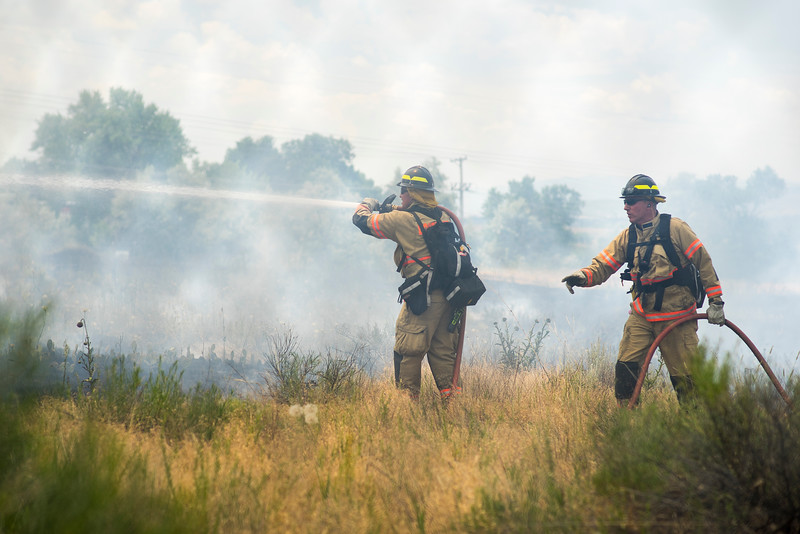 Firefighters fight a bushfire at 900 South Taft Avenue in a field between the Rocky Mountain Center for Technology and Innovation and the Thompson School District Building on June 29, 2016. The fire was started from a squirell that chewed through a power line that ran to a transformer on the ground.<br /> <br /> Photo by Michael Ortiz/ Loveland Reporter-Herald