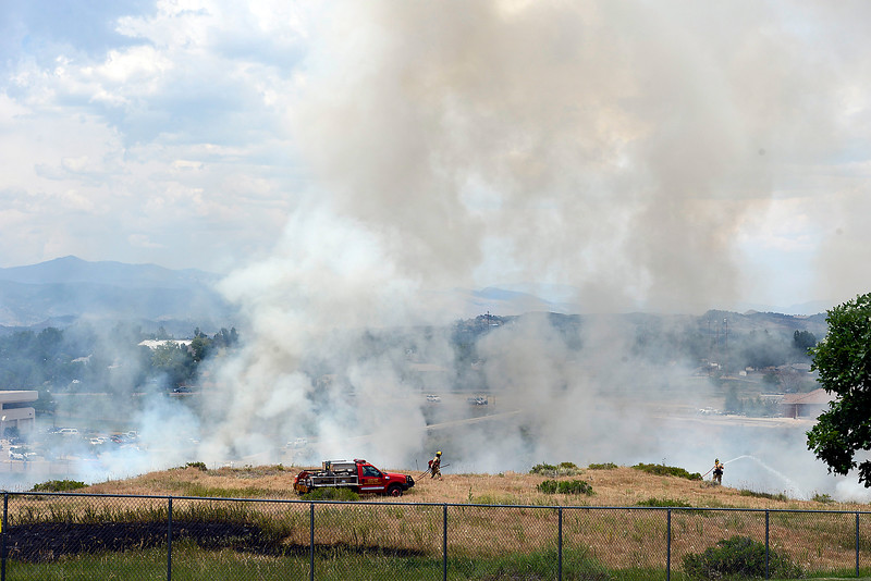 A firefighter sprays water on a brush fire Wednesday, June 29, 2016, in a field at 900 South Taft Avenue between the Thompson School District building and the Rocky Mountain Center for Technology and Innovation in Loveland. (Photo by Michael Ortiz/Loveland Reporter-Herald)