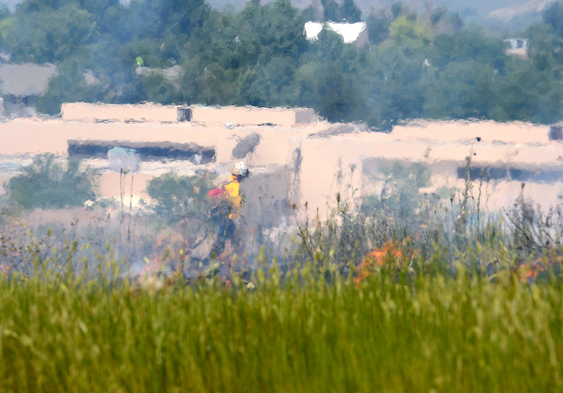 Heat waves from a brush fire distorts the image of a firefighter working to extinguish it Wednesday, June 29, 2016, in a field at 900 South Taft Avenue between the Thompson School District building and the Rocky Mountain Center for Technology and Innovation in Loveland. (Photo by Jenny Sparks/Loveland Reporter-Herald)