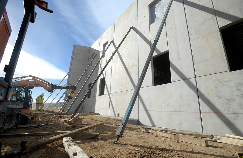 Nathan Williams, center left, assists Frank Sanchez, in the skid steer, far left, as they take down bars that support the pre fabricated concrete walls after they've been secured Friday, Dec. 30, 2016, at the new Loveland Classical School under construction in west Loveland. (Photo by Jenny Sparks/Loveland Reporter-Herald)