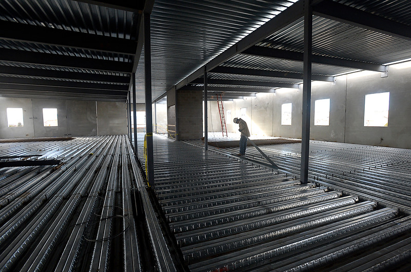 Standing on the second floor steel structure of the new Loveland Classical School, Arturo Lupian, prepares to weld in preparation for the concrete floors to go in Friday, Dec. 30, 2016, at the new school under construction in west Loveland. (Photo by Jenny Sparks/Loveland Reporter-Herald)