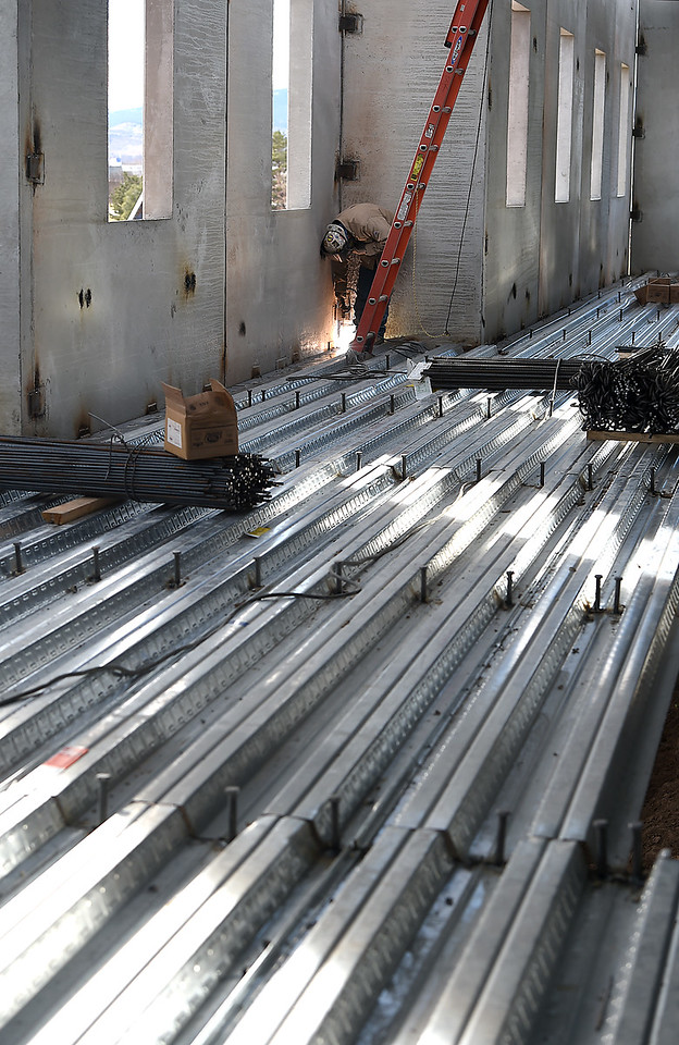 Standing on the second floor steel structure of the new Loveland Classical School, Arturo Lupian welds on the second floor Friday, Dec. 30, 2016, of the new Loveland Classical School under construction in west Loveland. (Photo by Jenny Sparks/Loveland Reporter-Herald)