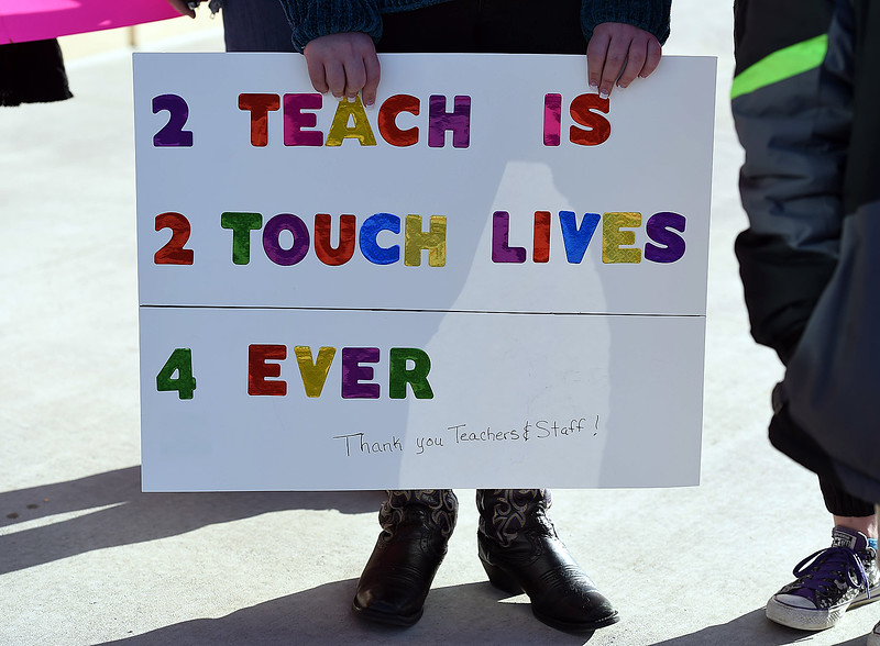 Loveland Classical Schools student Jessica Vannorsdel, 14, holds a sign in support of her teachers on Friday, April 27, 2018, as they arrive to school at Loveland Classical Schools upper school campus in Loveland. (Photo by Jenny Sparks/Loveland Reporter-Herald)