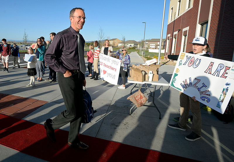 Loveland Classical Schools teacher Florian Hild smiles as he is surprised by students and parents cheering him and other teachers on Friday, April 27, 2018, as he arrives to school at Loveland Classical Schools upper school campus in Loveland. (Photo by Jenny Sparks/Loveland Reporter-Herald)