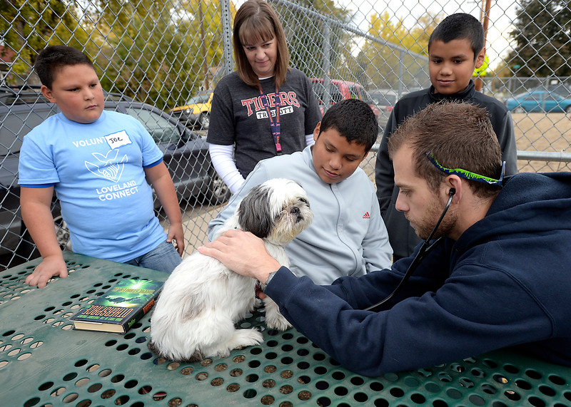 Vincent Panissidi, right, a Colorado State University Teaching Hospital student, listens to Scooby's heart as her owners Miguel Villegas, 12, center, and Omar Villegas, 10, right back, watch and wait to listen to her heart themselves Friday, Oct. 14, 2016, during the Loveland Connect event at Truscott Elementary School in downtown Loveland. Volunteer and Truscott prinicpal Karen Hanford, center left, and volunteer Joe Gaona, 11, far left, also watch.  (Photo by Jenny Sparks/Loveland Reporter-Herald)