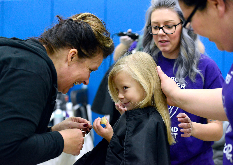 Bailey Taylor, 6, reacts as Denise Mitchell, left, director of Hair Dynamics Education Center, gives her a piece of candy while students Tori Fisher, center and Nikki Acosta cut her hair Friday, Oct. 14, 2016, during the Loveland Connect event at Truscott Elementary School in downtown Loveland. Loveland Connect is a one-stop shop of services for homeless and near homeless Loveland residents to learn what's available to help them out with things like housing, food and clothing.  (Photo by Jenny Sparks/Loveland Reporter-Herald)