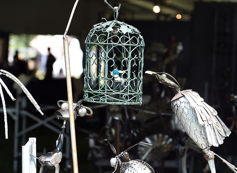 "A sculpture made with recycled and found objects by artist Mike Combs titled ""The Bird Cage"" depicts a bird peering into a bird cage with a human figure on a swing inside Friday, Aug. 10, 2018,  during the Loveland Fine Art Invitational at Loveland High School.   (Photo by Jenny Sparks/Loveland Reporter-Herald)"