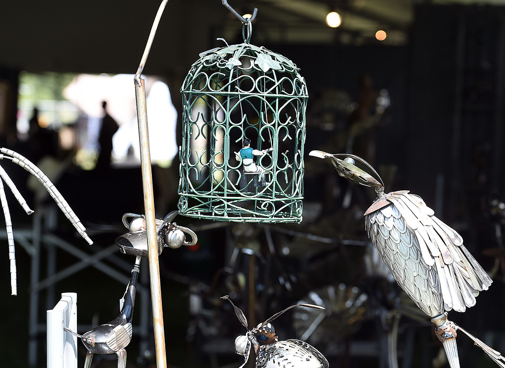 ". A sculpture made with recycled and found objects by artist Mike Combs titled ""The Bird Cage\"" depicts a bird peering into a bird cage with a human figure on a swing inside Friday, Aug. 10, 2018,  during the Loveland Fine Art Invitational at Loveland High School.   (Photo by Jenny Sparks/Loveland Reporter-Herald)"