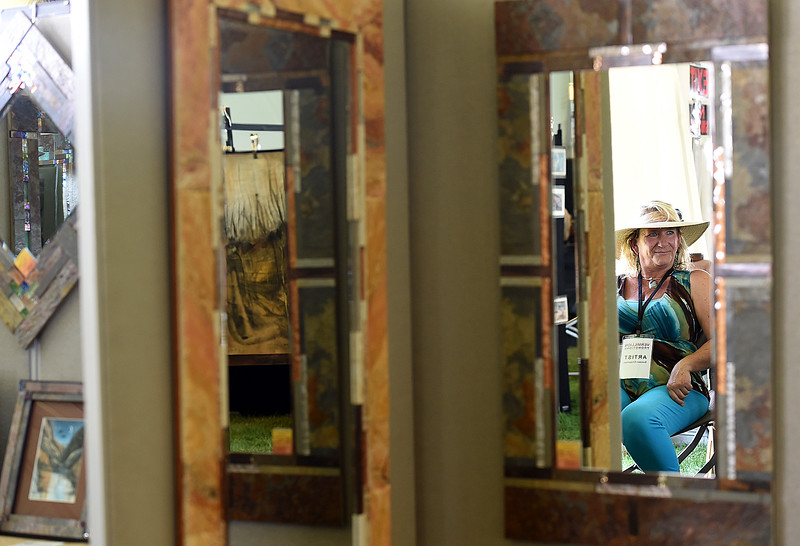 Suezan Chapman is reflected in one of the mirrors she created for sale Friday, Aug. 10, 2018, during the Loveland Fine Art Invitational at Loveland High School.   (Photo by Jenny Sparks/Loveland Reporter-Herald)