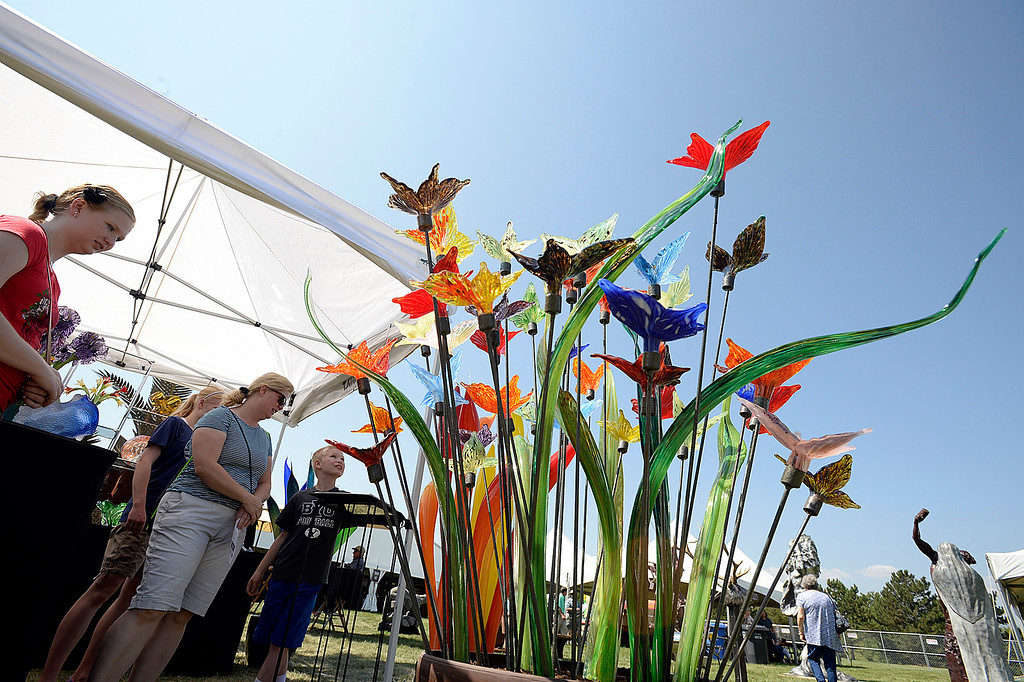 . Members of the Valentine family check out some of the blown glass sculptures Friday, Aug. 10, 2018, by artist Joshua Noah Dopp during the Loveland Fine Art Invitational at Loveland High School. From left are Emma Valentine, 16, Anne Valentine, 14, Laura Valentine, and John Valentine, 9.   (Photo by Jenny Sparks/Loveland Reporter-Herald)
