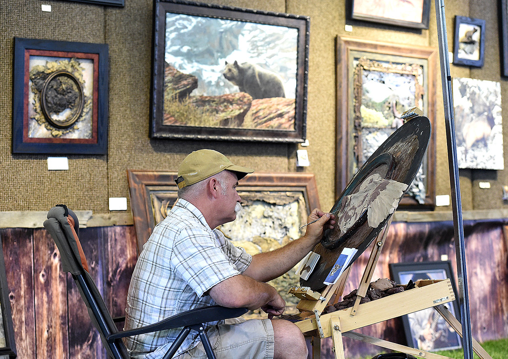 ". Artist Chip Jones ""builds a canvas\"" with petroleum clay and wax Friday, Aug. 10, 2018, during the Loveland Fine Art Invitational at Loveland High School. Jones, who owns Bigrock Bronze foundry in Montana, uses a kind of bass relief process with bronze while making his art. \""My brushes are castings and my paint is 2,300 degrees. You kind of have to be silly and crazy to splash and throw bronze,\"" he said while talking about how he breaks the rules with bronze.   (Photo by Jenny Sparks/Loveland Reporter-Herald)"
