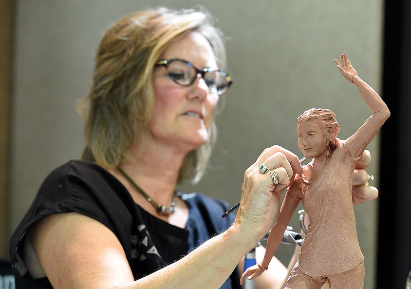 Artist Pamela Winters sculpts a piece in clay trying to convey balance and focus Friday, Aug. 10, 2018, during the Loveland Fine Art Invitational at Loveland High School. Winters said the piece sort of turned into a self portrait symbolizing her beating cancer.   (Photo by Jenny Sparks/Loveland Reporter-Herald)