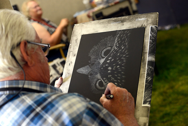 Loveland artist Rich Cayou works on a scratch board piece Friday, Aug. 12, 2016, at his booth during the Loveland Fine Art and Wine Festival outside Loveland High School in Loveland.  (Photo by Jenny Sparks/Loveland Reporter-Herald)