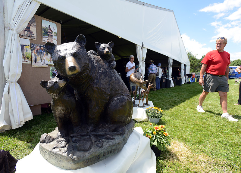 "Dave Hedblom, right, and his wife, Judy, left, walk past bronze sculptures Friday, Aug. 12, 2016, at the Loveland Fine Art and Wine Festival outside Loveland High School in Loveland. The bear sculpture titled ""Bear Hugs"" is by Scy Caroselli and the deer sculpture is by her mother Marianne Caroselli.  (Photo by Jenny Sparks/Loveland Reporter-Herald)"