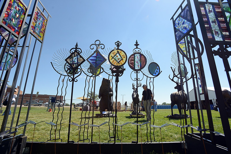 Loveland artist Alex Palkovich is framed by Roger Mathew's stained glass art as he checks out sculptures Friday, Aug. 12, 2016, at the Loveland Fine Art and Wine Festival outside Loveland High School in Loveland. The Loveland Fine Art and Wine Festival, which goes from 10 am- 5pm Friday through Sunday, is one of three events where peolpe can enjoy art this weekend in Loveland. The other events are Sculpture in the Park and Art in the Park. (Photo by Jenny Sparks/Loveland Reporter-Herald)