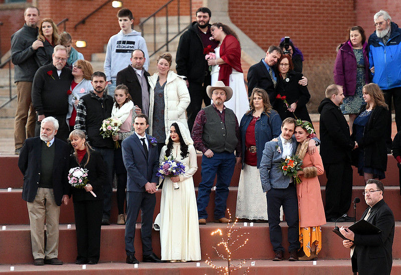 Brides and grooms, including John and Kristen Overheim, front center left, and Tim and Stephanie O'Rourke, front center right, all of Loveland, listen to a reading during a group wedding ceremony Wednesday, Feb. 14, 2018, at Foote Lagoon in downtown Loveland. Eleven couples married and 12 renewed their vows. (Photo by Jenny Sparks/Loveland Reporter-Herald)