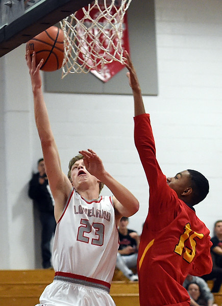 Loveland High's #23 Jake Kolb goes up for a shot as Northglenn's #15 Tynan Burbank tries to block during their game at Loveland High School on Friday, Dec. 16, 2016. (Photo by Jenny Sparks/Loveland Reporter-Herald)