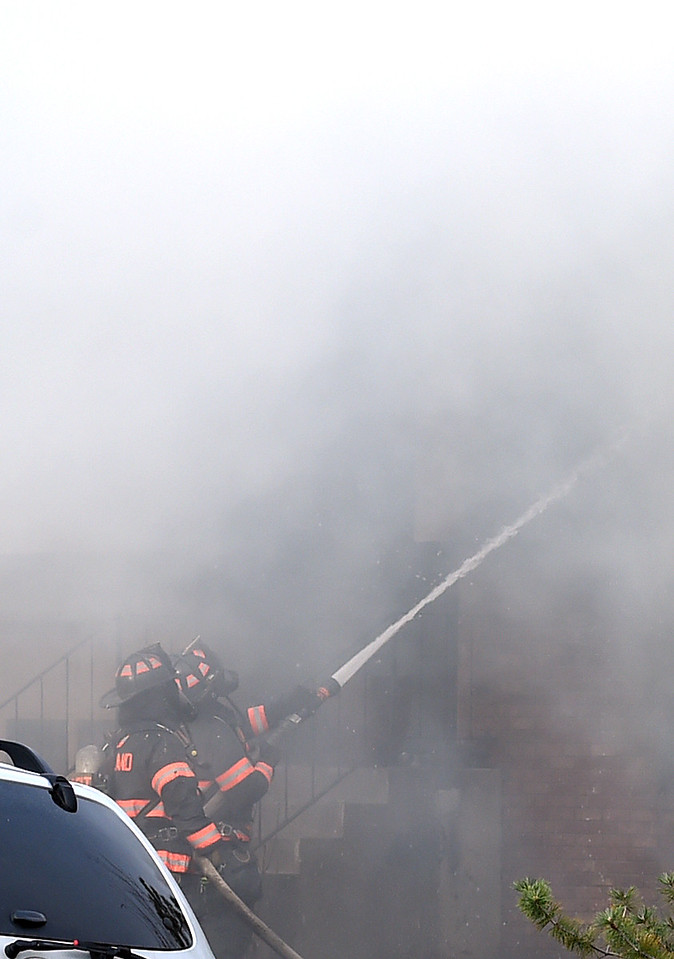 Loveland Fire Rescue Authority firefighters spray water on a house fire Saturday, March 25, 2017, at 2516 Estrella Ave. in west Loveland.  (Photo by Jenny Sparks/Loveland Reporter-Herald)