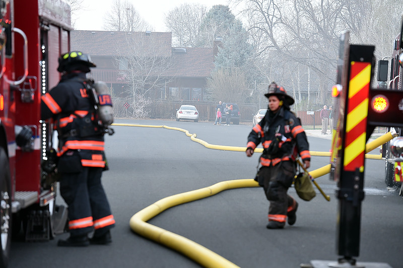A fire hose leads to a hydrant as neighbors watch Loveland Fire Rescue Authority firefighters battle a house fire Saturday, March 25, 2017, at 2516 Estrella Ave. in west Loveland.  (Photo by Jenny Sparks/Loveland Reporter-Herald)