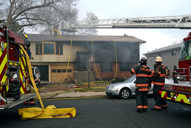 Loveland Fire Rescue Authority firefighters attack a house fire Saturday, March 25, 2017, at 2516 Estrella Ave. in west Loveland.  (Photo by Jenny Sparks/Loveland Reporter-Herald)