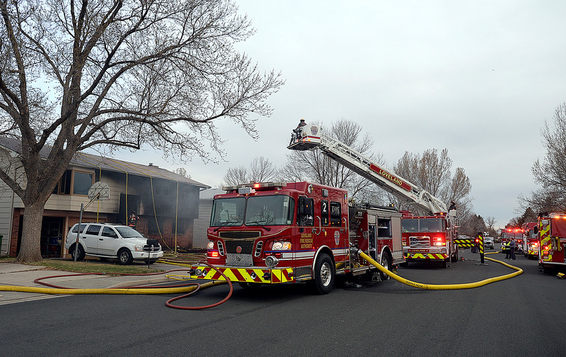 Loveland Fire Rescue Authority firefighters battle a house fire Saturday, March 25, 2017, at 2516 Estrella Ave. in west Loveland. With the help of Tower 6, their ladder truck, firefighters access the roof to use fog nail nozzles that spray water into the attic. (Photo by Jenny Sparks/Loveland Reporter-Herald)