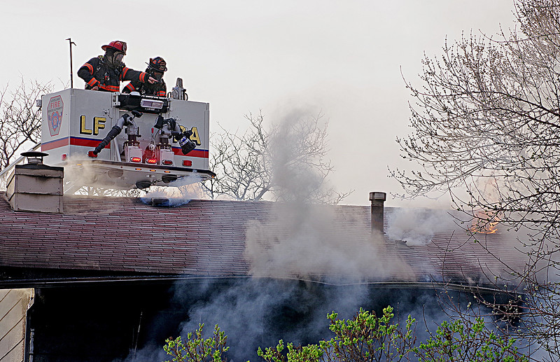 Loveland Fire Rescue Authority firefighters attack a house fire Saturday, March 25, 2017, at 2516 Estrella Ave. in west Loveland. (Photo by Jeff Stahla/Loveland Reporter-Herald)