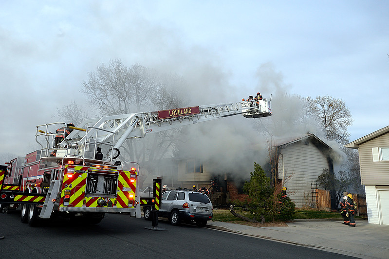 Loveland Fire Rescue Authority firefighters battle a house fire Saturday, March 25, 2017, at 2516 Estrella Ave. in west Loveland. With the help of Tower 6, their ladder truck, firefighters access the roof to use fog nail nozzles that spray into the attic. (Photo by Jenny Sparks/Loveland Reporter-Herald)