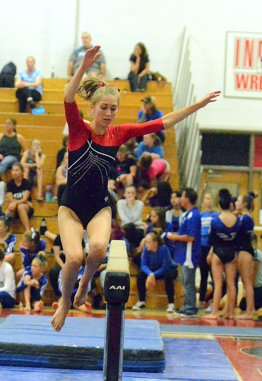 . Loveland\'s Hannah White jumps onto the balance beam at the Loveland Invitational gymnastics meet Friday at LHS. (Mike Brohard/Loveland Reporter-Herald)