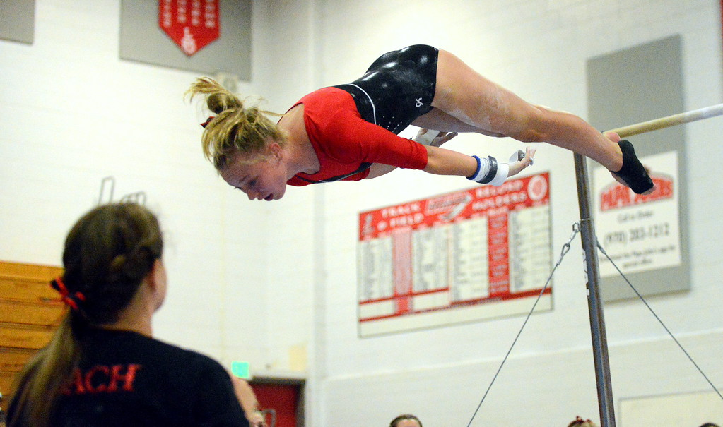 . Loveland coach Jessica Toomey watches as Silje Haehre finds the floor during her dismount from the uneven bars at the Loveland Invitational gymnastics meet Friday at LHS. (Mike Brohard/Loveland Reporter-Herald)