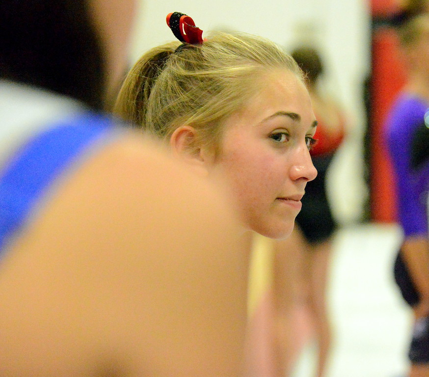 . Loveland\'s Hannah White watches floor routines as the Indians await their turn on the uneven bars at the Loveland Invitational gymnastics meet Friday at LHS. (Mike Brohard/Loveland Reporter-Herald)