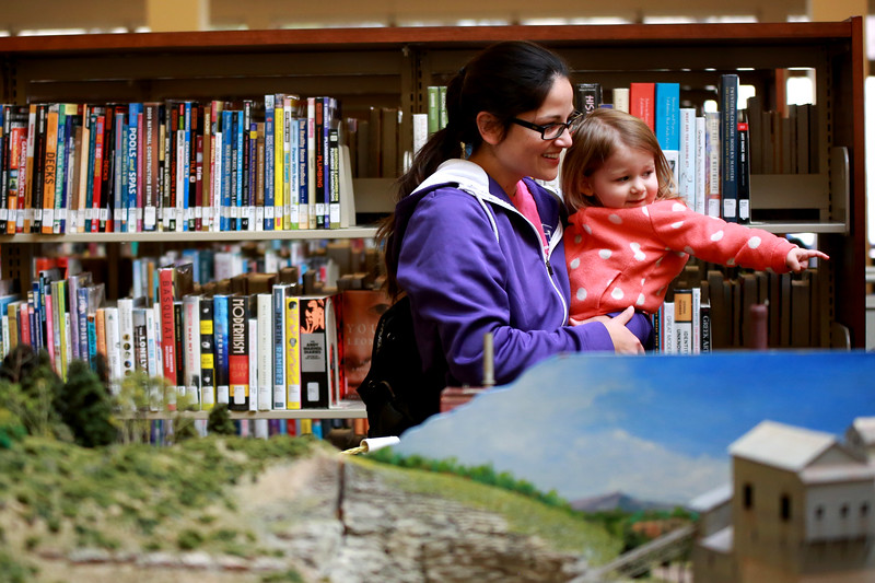 Allison Gerrish holds her daughter Elena, 2, as they view the model train village from the Northern Colorado Model Railway Club display during the Loveland Lights Celebration at the Loveland Public Library on Dec. 8, 2018 in Loveland, Colo. <br /> Photo by Taelyn Livingston/ Loveland Reporter-Herald