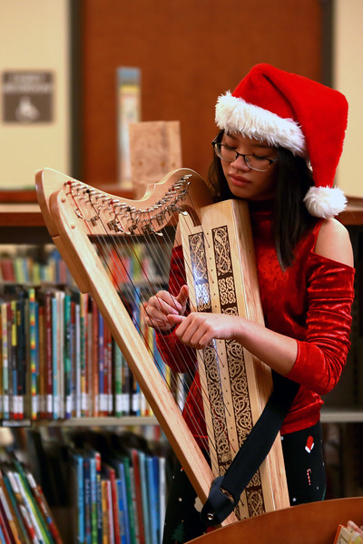 Lia Rudeen, 15, of Longmont plays the harp during the Loveland Lights Celebration at the Loveland Public Library on Dec. 8, 2018 in Loveland, Colo. <br /> Photo by Taelyn Livingston/ Loveland Reporter-Herald