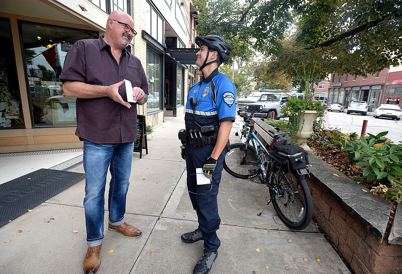 Loveland Police officer Jay Smith, right, chats with Clay Caldwell, left, owner of Mo' Betta Gumbo, while patrolling Fourth Street on bicycle Friday, Sept. 29, 2017, in downtown Loveland. (Photo by Jenny Sparks/Loveland Reporter-Herald)