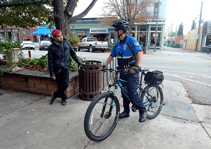 Loveland Police officer Jay Smith, right, chats with Peter Unpingco, left, as he patrols Fourth Street on bicycle Friday, Sept. 29, 2017, in downtown Loveland. (Photo by Jenny Sparks/Loveland Reporter-Herald)