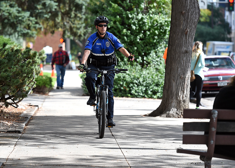 Loveland Police officer Jay Smith waves to people on a bench as he patrols Sixth Street on bicycle Friday, Sept. 29, 2017, in downtown Loveland. (Photo by Jenny Sparks/Loveland Reporter-Herald)