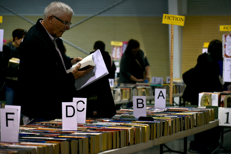Dennis Burchett, from Windsor, skims through a book before adding it to his bag during Loveland Public Library's Spring Book Sale on Friday, April 20, 2018 at The Ranch in Loveland. Photo by Thieng Mai/Loveland Reporter-Herald.