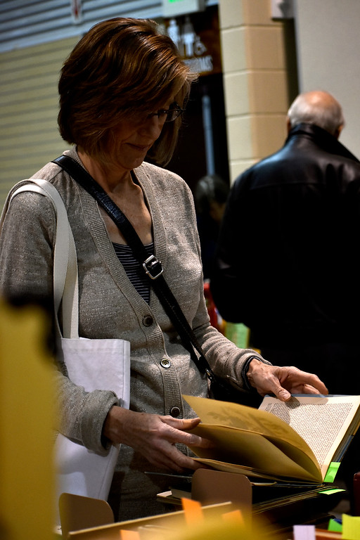 . Janice Long, from Loveland, looks through a book to decide on a purchase during Loveland Public Library\'s Spring Book Sale on Friday, April 20, 2018 at The Ranch in Loveland. Photo by Thieng Mai/Loveland Reporter-Herald.