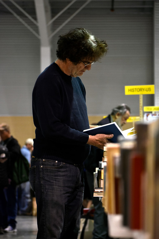 . Mike Riordan, from Colorado Springs, flipping through a history book that had caught his eye at Loveland Public Library\'s Spring Book Sale on Friday, April 20, 2018 at The Ranch in Loveland. Photo by Thieng Mai/Loveland Reporter-Herald.