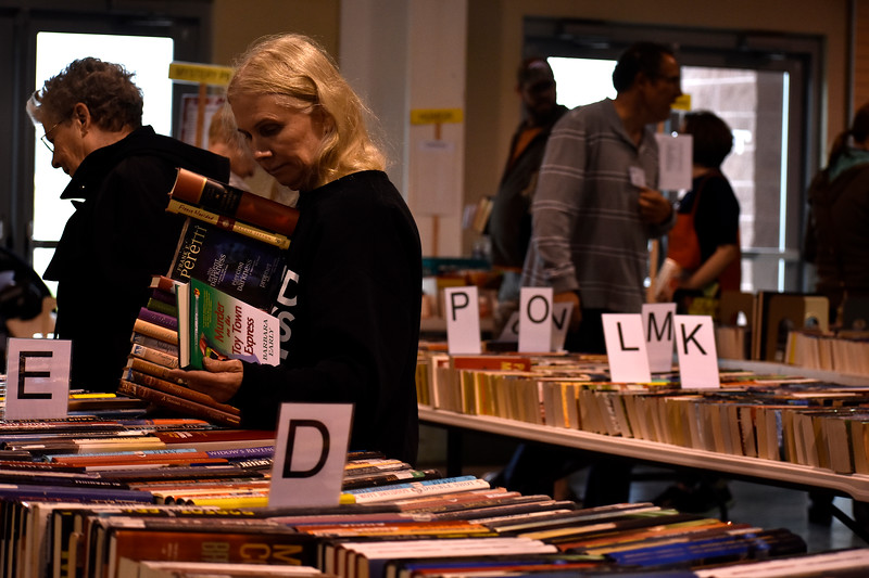 Marcie Tichenor, from Aurora, considering another book to add onto her growing stack during Loveland Public Library's Spring Book Sale on Friday, April 20, 2018 at The Ranch in Loveland. Photo by Thieng Mai/Loveland Reporter-Herald.