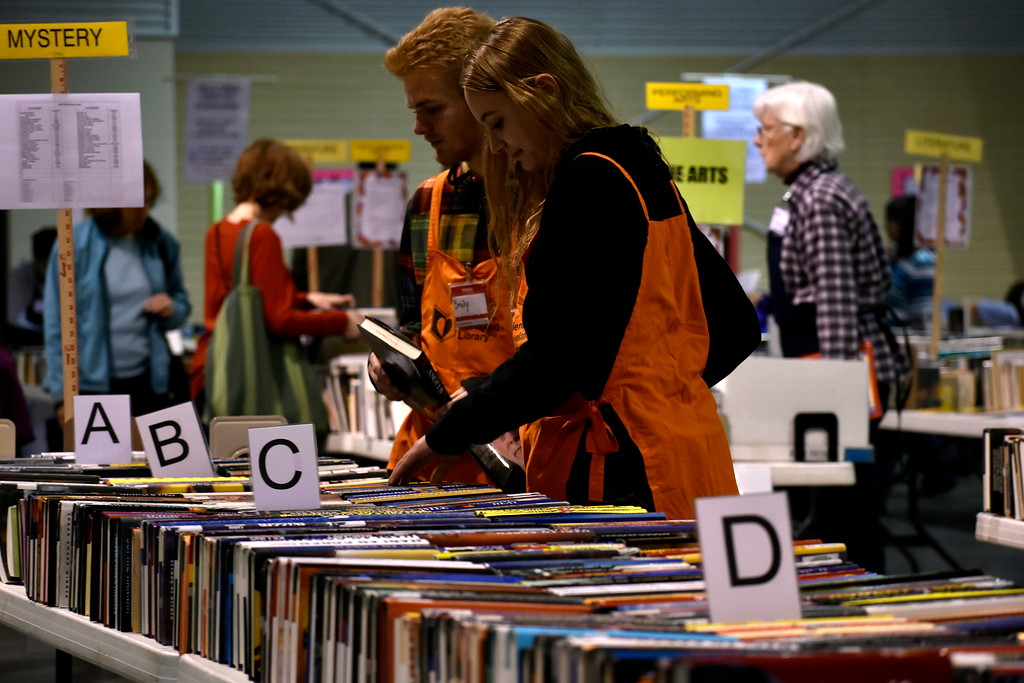. Volunteers Camiren Meyers (15, left) and Emily Silver (14, right) restock more books to sell during Loveland Public Library\'s Spring Book Sale on Friday, April 20, 2018 at The Ranch in Loveland. Meyers and Silver both attend Mountain View High School in Loveland. Photo by Thieng Mai/Loveland Reporter-Herald.