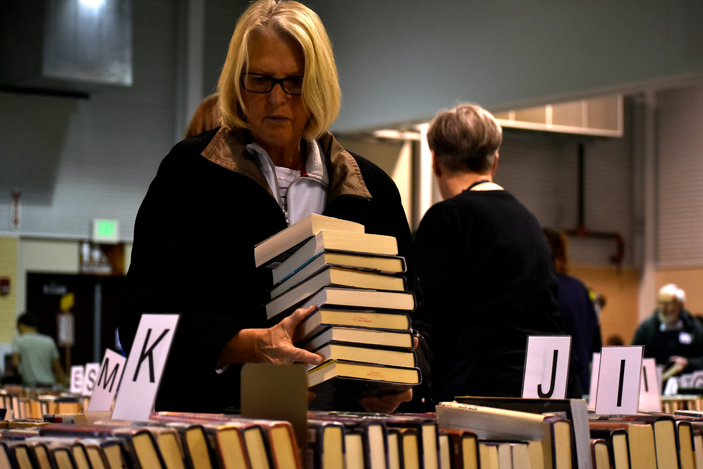 . Pat Barscher, of Loveland, perusing to add more titles to her stack of books at Loveland Public Library\'s Spring Book Sale on Friday, April 20, 2018 at The Ranch in Loveland. Photo by Thieng Mai/Loveland Reporter-Herald.
