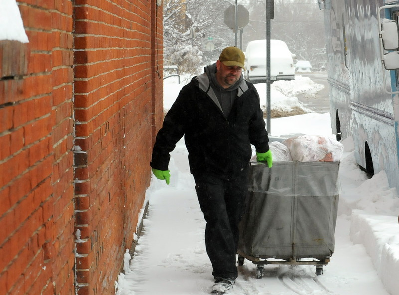 Loveland Steam Laundry employee Josh Finstad pulls a cart filled with clean linens to a truck outside the downtown Loveland business Tuesday morning. The 12-plus inches of snow that fell on the city wasn't going to stop him from making his deliveries to retirement centers, hotels and restaurants in the area. (Photo by Craig Young/Loveland Reporter-Herald)
