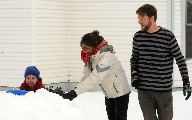 Max Madden and Becca Hughes play with their 3-year-old son, Finn, in the snow in front of their house in the 400 block of East Third St. on Tuesday morning. Madden was shoveling out after a snowstorm dropped more than a foot of snow on the city. (Photo by Craig Young/Loveland Reporter-Herald)