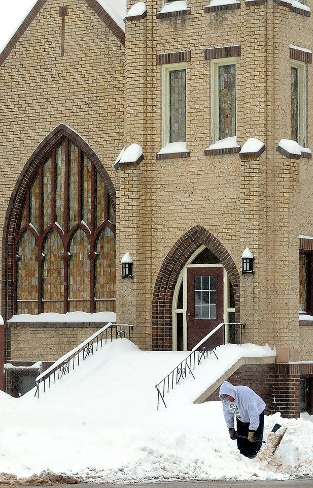 Stephen Patton shovels snow off the sidewalk Tuesday morning, Feb. 2, 2016, in front of Emmanuel Baptist Church at the corner of Third Street and Jefferson Avenue in downtown Loveland. Patton lives next door to the church, and his father-in-law, the Rev. Bob Garner, is the pastor of Emmanuel  Baptist. (Photo by Craig Young/Loveland Reporter-Herald)