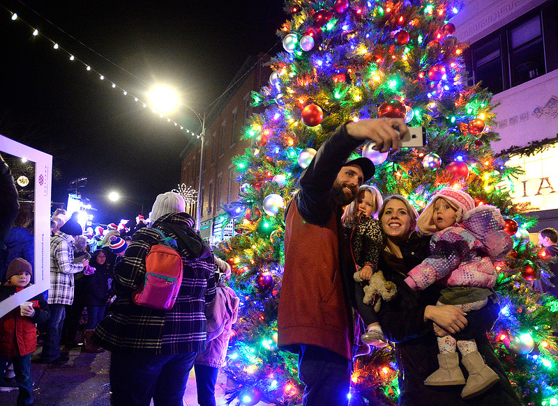 Doug Mangeris, left, holding his daughter Kennidy Santillanes, and Katelynne Mispagel, holding her daughter Zaylynne Truax, pose for a selfie in front of the Christmas tree Wednesday, Nov. 29, 2017, during the Festival of Lights on Fourth Street in downtown Loveland.    (Photo by Jenny Sparks/Loveland Reporter-Herald)